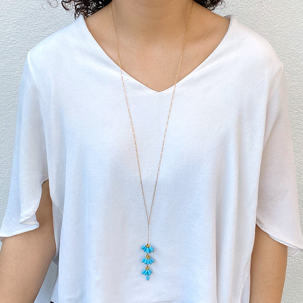Woman wearing gold chain necklace with pendant of 3 bunches turquoise beads with single bead at end.