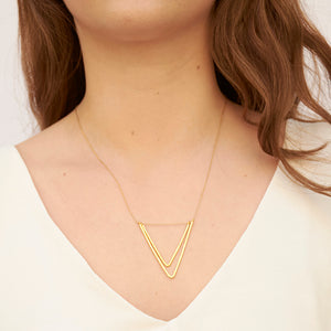 Woman wearing delicate gold chain necklace with two nested v-shaped pendants.
