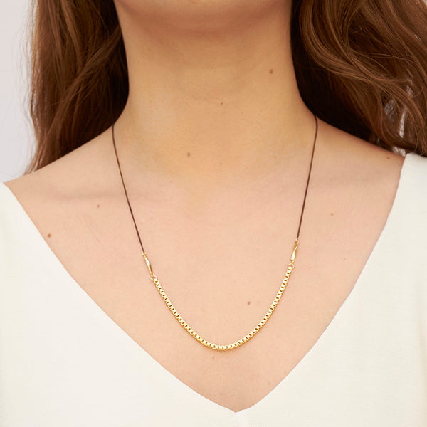 Woman wearing necklace with black upper chain and gold box chain on the bottom.