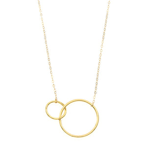 Close-up of delicate gold chain necklace with small and large interlocking circles as pendant.