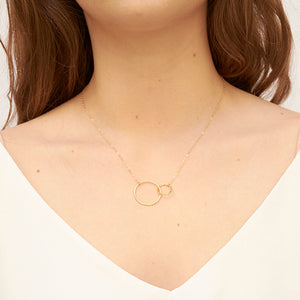 Woman wearing gold chain necklace with small and large interlocking circles as pendant.