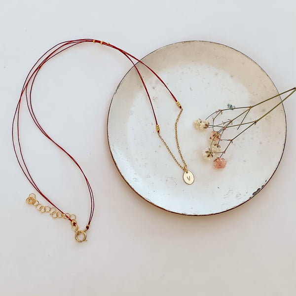 Delicate red thread necklace with gold chain and oval pendant on small plate.