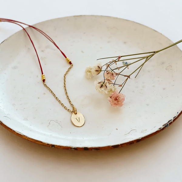 Close-up of delicate red thread necklace with gold chain and oval pendant on plate with small flowers.