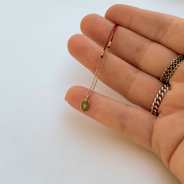 Close-up of fingers with delicate red thread necklace with gold chain and oval pendant.
