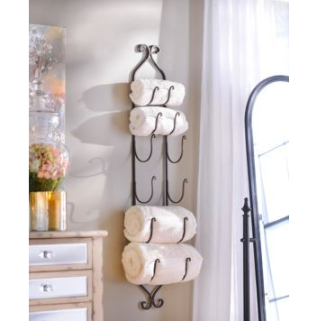 Think outside the box. A wall mounted wine rack works perfectly for holding rolled towels. Decorative and useful!