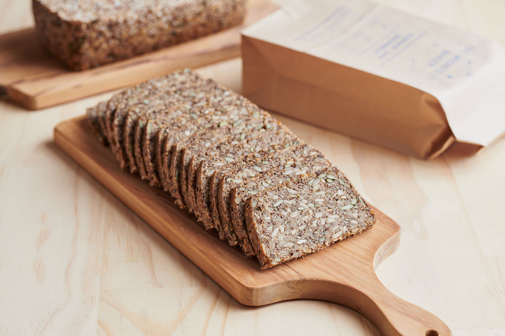 A Buckwheat Freedom Loaf, fully sliced.  The slices are neatly stacked on a wooden chopping board in a row.  In the background is a full unsliced loaf and a loaf wrapped up in it's brown paper bag.