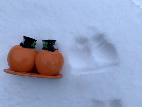 the peach brothers figurine buried in snow, beside the snow angel of itself