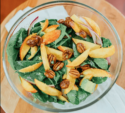 fresh, crisp salad with spinach, pecans, fresh peaches, avocado, and drizzled with a balsamic vinaigrette dressing