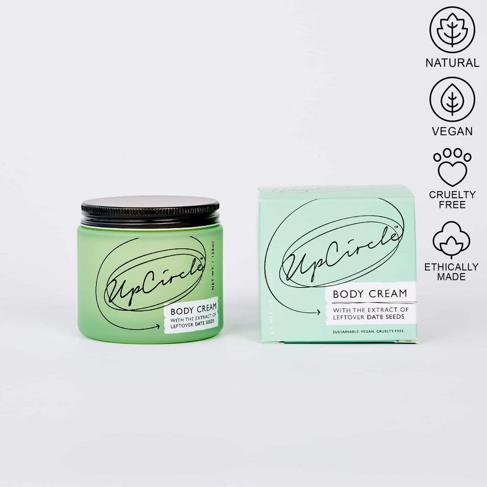 upcirlce body cream green jar next to packaging