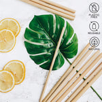 large bamboo straws laying over leaf with lemons nearby