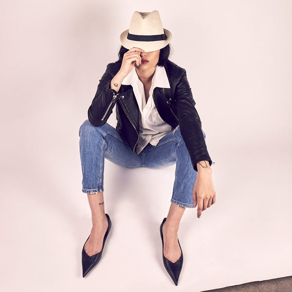 woman with fedora hat over her eyes wearing peg legged denim and black leather jacket styled in Lou Earl black pointed leather flat shoes
