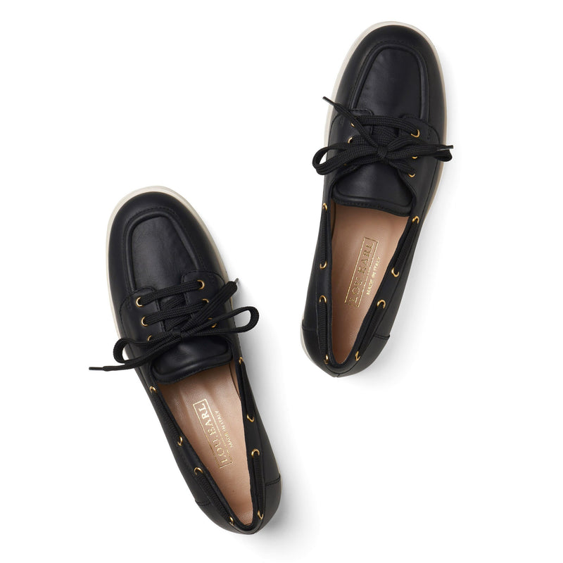 womens sporty tailored black leather boat shoes with black laces and stand-out gold metal plated eyelets. insole is nude lambskin leather with gold foil emboss Lou Earl logo. Photo shows hint of white outsole.