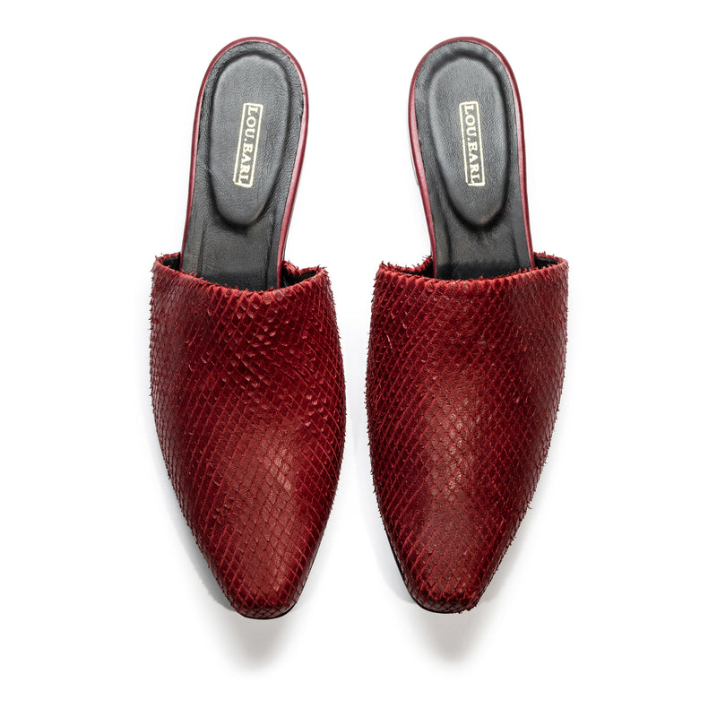 Pair of women's mule shoes in striking oxblood color, made of laser-cut leather. Upper is very simple consisting only of textured leather. Lining is black leather on cushioned footbed with gold logo.