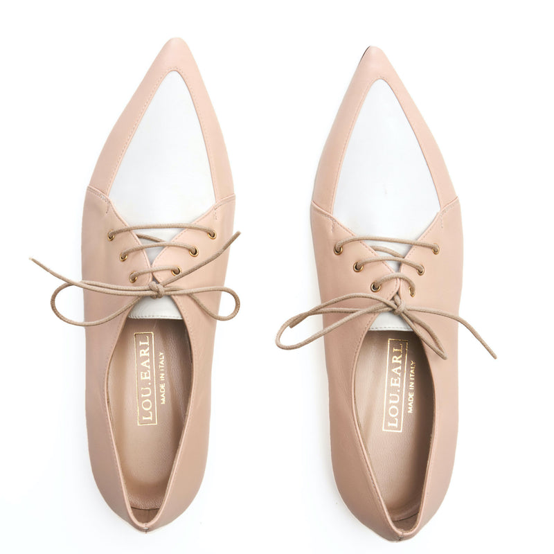 "a pair of womens nude leather shoes featuring a pointed toe. upper vamp is contrast white leather in a ""V"" shape. Laces are round and small. insole is nude lambskin leather with gold foil logo."