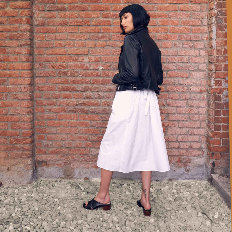 Indian woman wearing white skirt and black leather biker jacket with black crisscross slide mule heels in front of brick background standing on rocks