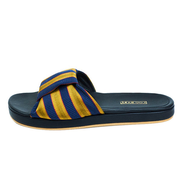 Gold and navy striped sandal with striped bow tie at vamp. Leather footbed is contoured with leather outsole.