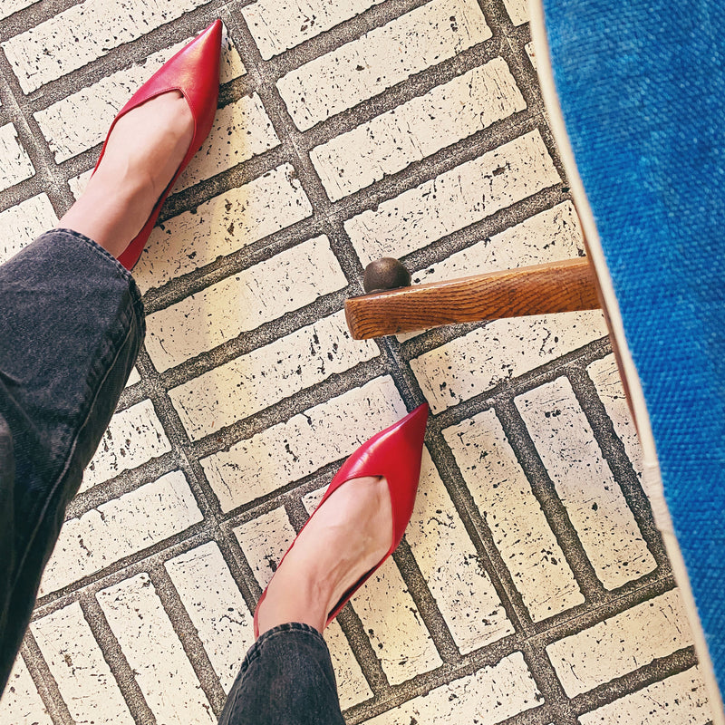 very pointy flat shoes made of leather in a bright lipstick red color.