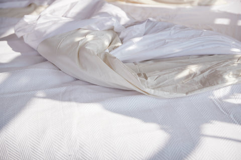 Bed with Organic cotton bedsheets and white color blanket