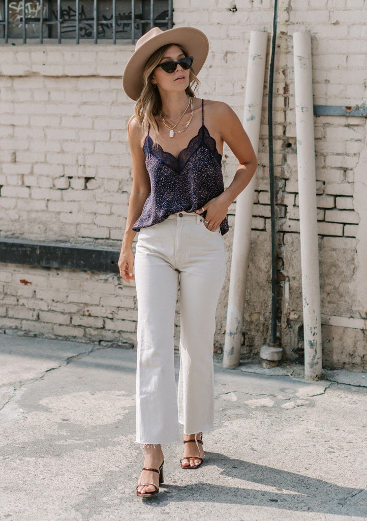 [Color: Navy Tan] A luxuriously soft and silky slip camisole. Perfect for layering, this flirty tank top features romantic lace trim and a flattering drape. Styled here with off white flared denim and heeled sandals.