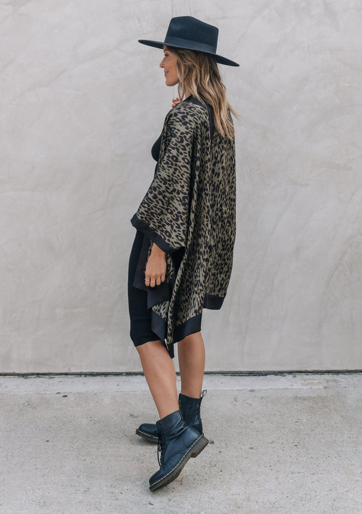 [Color: Army Black] A woman standing outside wearing a mid length leopard print kimono with half length kimono sleeves, an open front, and side slits.