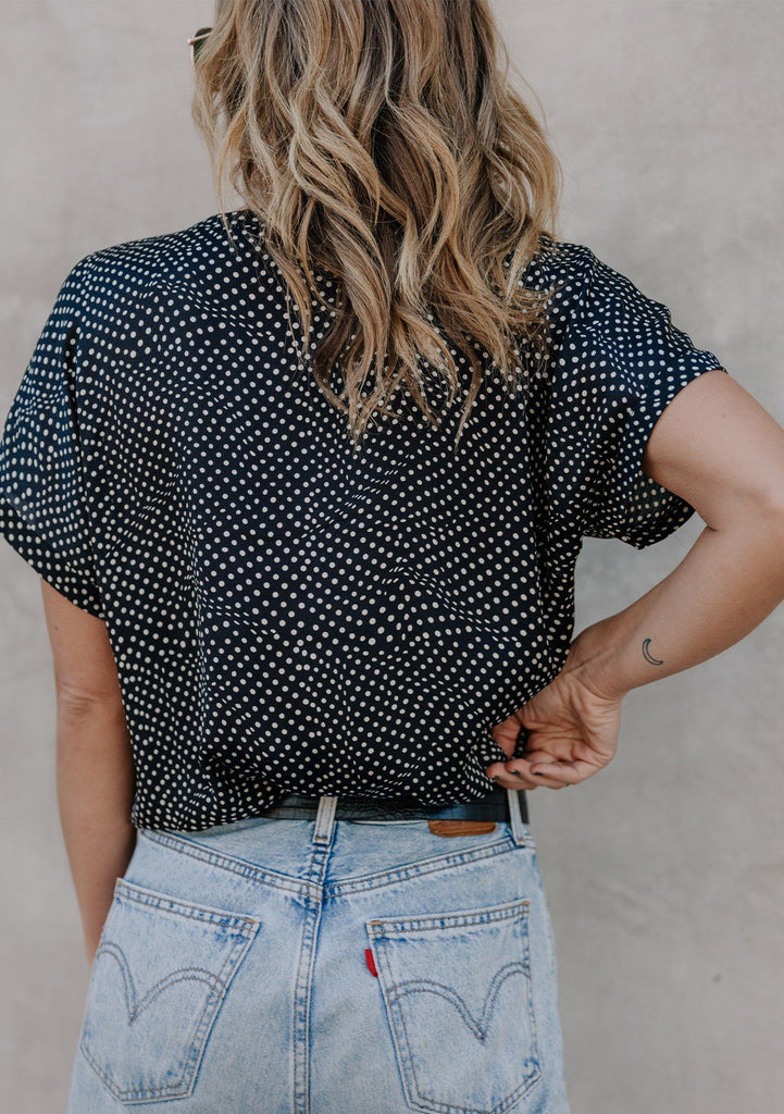 [Color: Black/Ivory] A blond woman wearing a classic French inspired silky polka dot blouse. Featuring a banded collar, short dolman sleeves with a folded cuff, and a sophisticated front pleat.