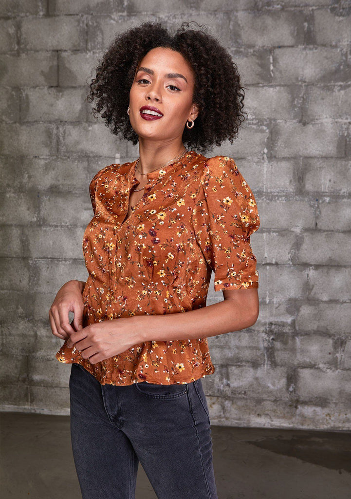[Color: Caramel] A woman wearing a soft and silky button front top. Featuring a small floral print throughout and a half sleeve with a puffed shoulder.