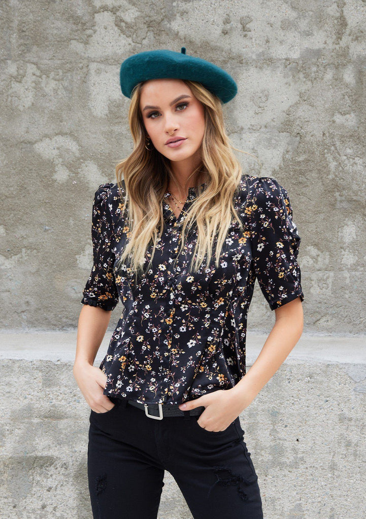 [Color: Black] A woman wearing a soft and silky button front top. Featuring a small floral print throughout and a half sleeve with a puffed shoulder.