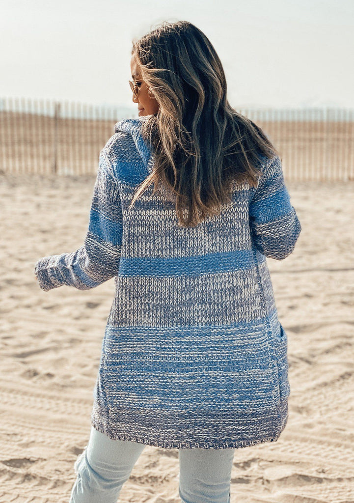[Color: Denim Blue] Girl at the beach wearing a zipper front striped cardigan.