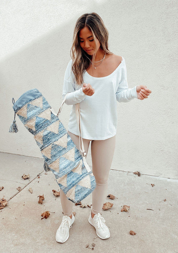 [Color: Denim Natural] A geometric patterned yoga mat bag made from upcycled denim. Featuring a side water bottle pouch, a tassel drawstring closure, and an adjustable crossbody strap.