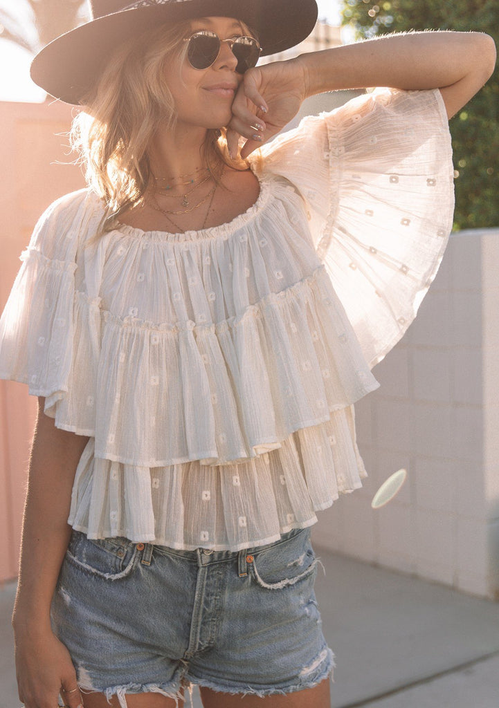 [Color: Off White] Beautiful bohemian tiered sheer layer off shoulder blouse with eyelet details. This flowy, white bohemian blouse can be dressed up with a skirt, or wear it with your favorite cut off shorts!