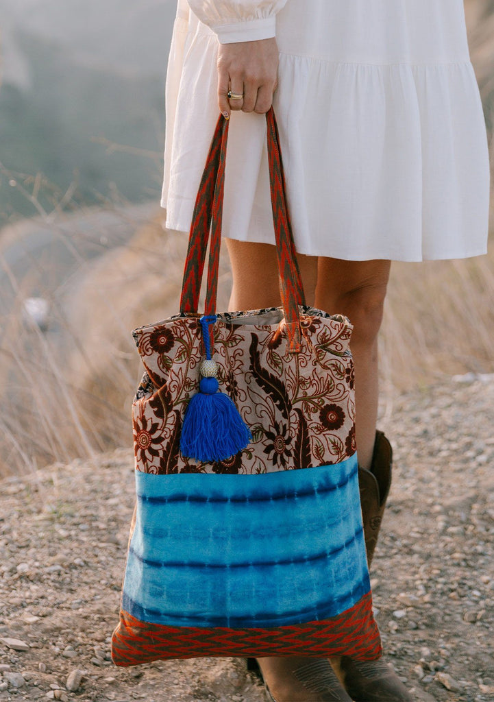 [Color: Natural/Blue] A woman standing outside on a cliff wearing a white dress and holding a bohemian tie dye patchwork tote bag. Featuring a large tassel accent.