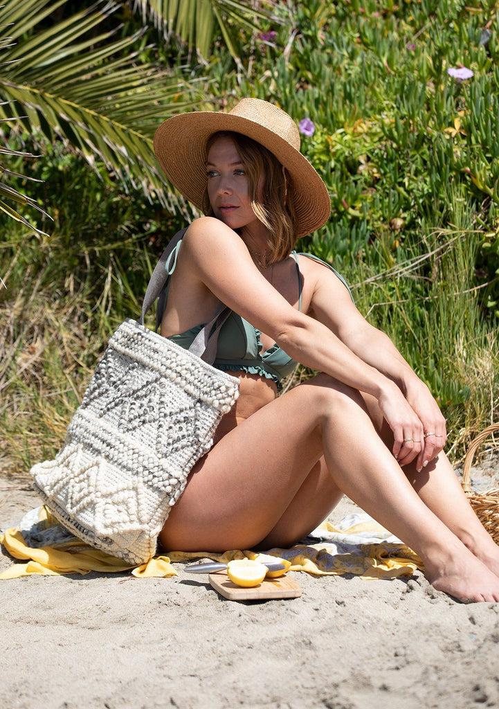 [Color: Taupe Combo] A woman on the beach wearing a bikini holding an Ombre diamond patterned carpet tote bag.