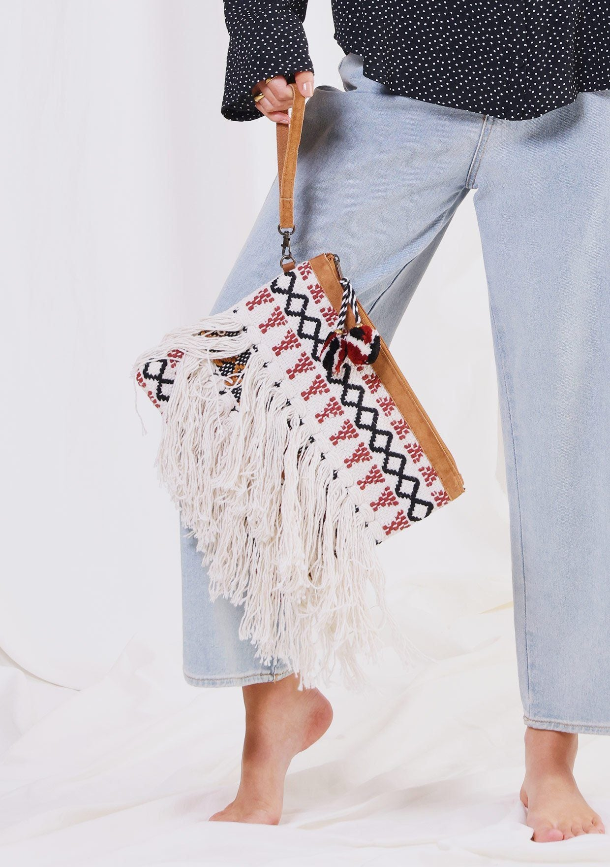 [Color: Natural/Spice] A woman holding a large suede trimmed clutch. Featuring an ultra-bohemian fringed front and a zippered pull closure with a pom accent.