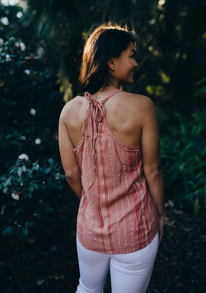 [Color: Dusty Rose] A brunette woman standing outside wearing a metallic lurex stripe tank top. Featuring a racerback detail, an adjustable tie neck, and a v neckline.
