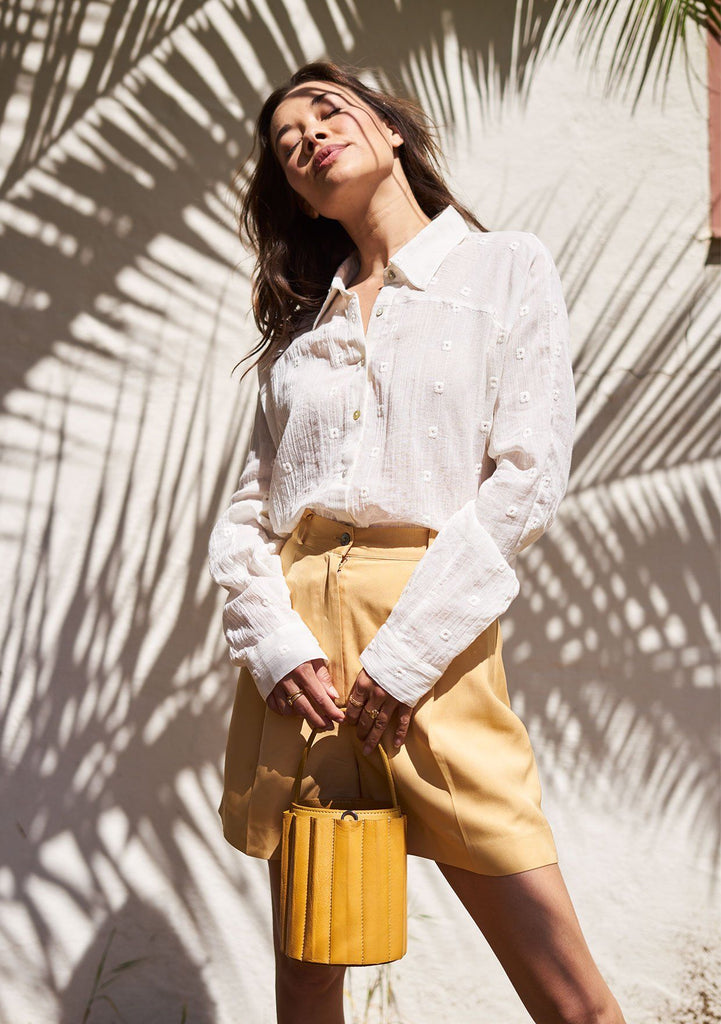 [Color: Off White] A woman standing outside wearing a sheer gauze long sleeve button up shirt. Featuring a cross yoke detail in the back, side slits, and embroidered details throughout.