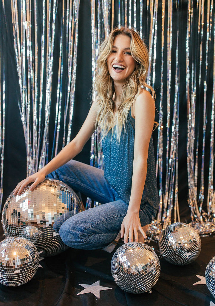 [Color: Slate Blue] A blond woman wearing a soft and silky slate blue star jacquard lace trim camisole and holding a disco ball.
