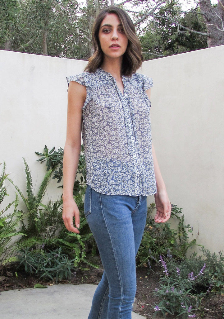 [Color: Denim/Ivory] A brunette woman standing outside wearing a dreamy sheer ditsy floral button front top. Featuring ruffled cap sleeves, a ruffled high neckline, and neckties.