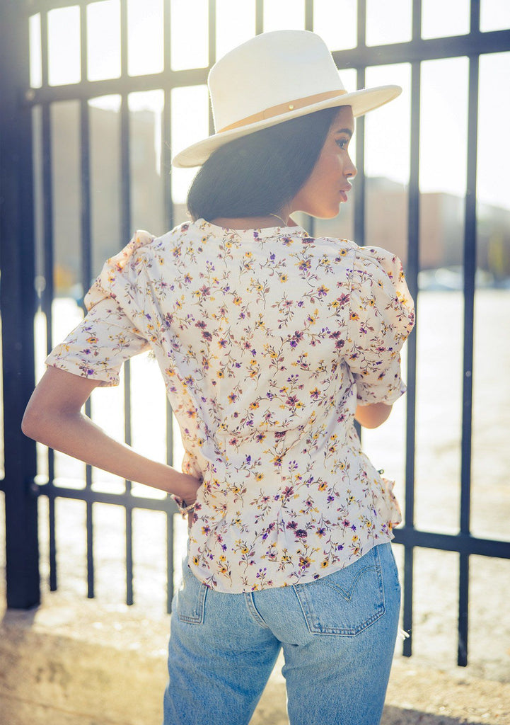 [Color: Dusty Blush] A woman wearing a soft and silky button front top. Featuring a small floral print throughout and a half sleeve with a puffed shoulder.