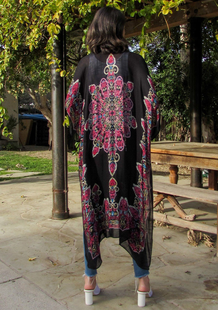 [Color: Black/Raspberry] A brunette woman standing poolside wearing a lightweight bohemian kimono. Featuring a medallion print design, half length kimono sleeves, side slits, and an open front.