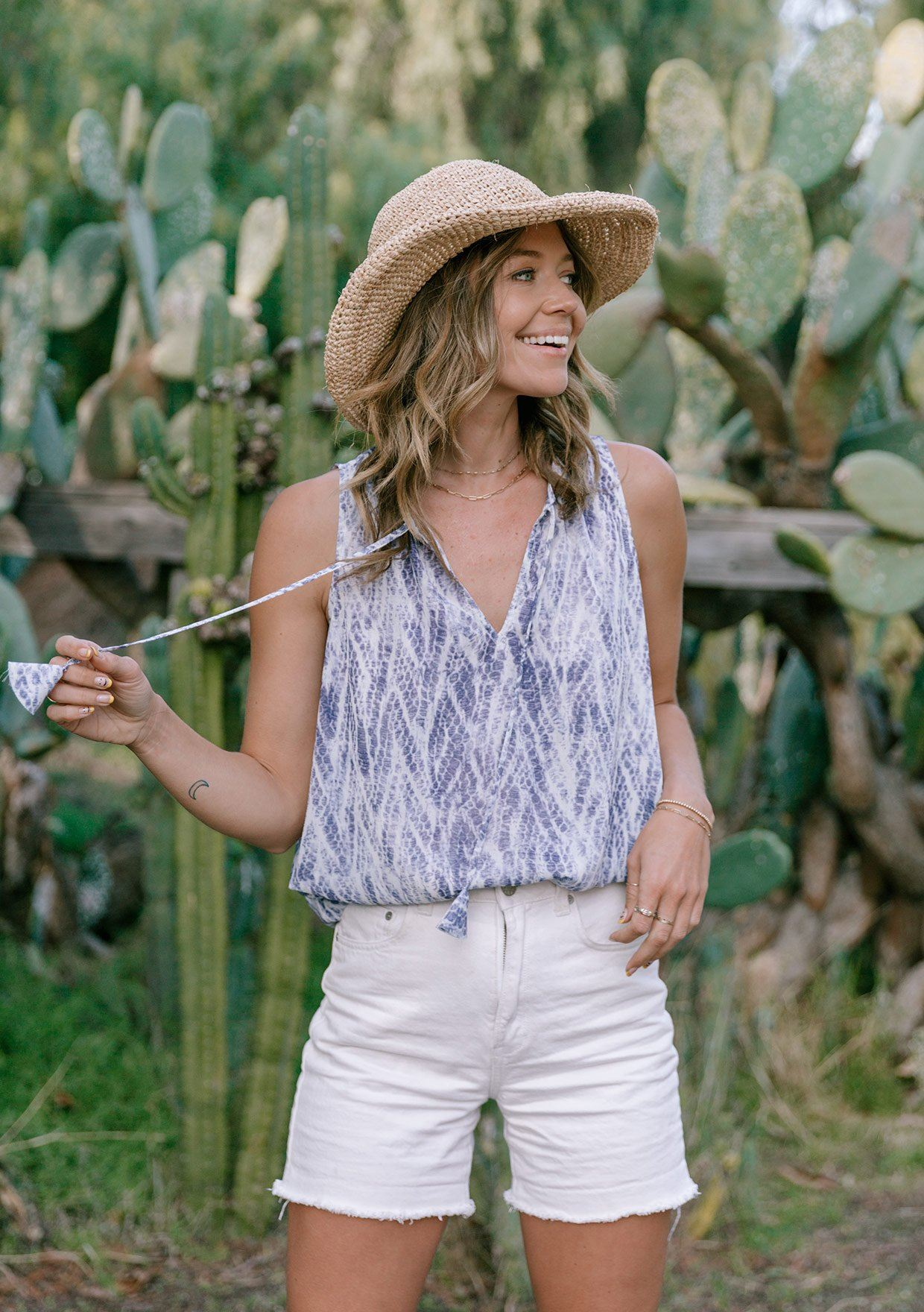 [Color: Iris] A woman standing in front of a field of cacti wearing a classic and flattering sleeveless blouse in iris blue abstract chevron pattern. Features a split neckline, a shirttail hemline, and a side button up detail.