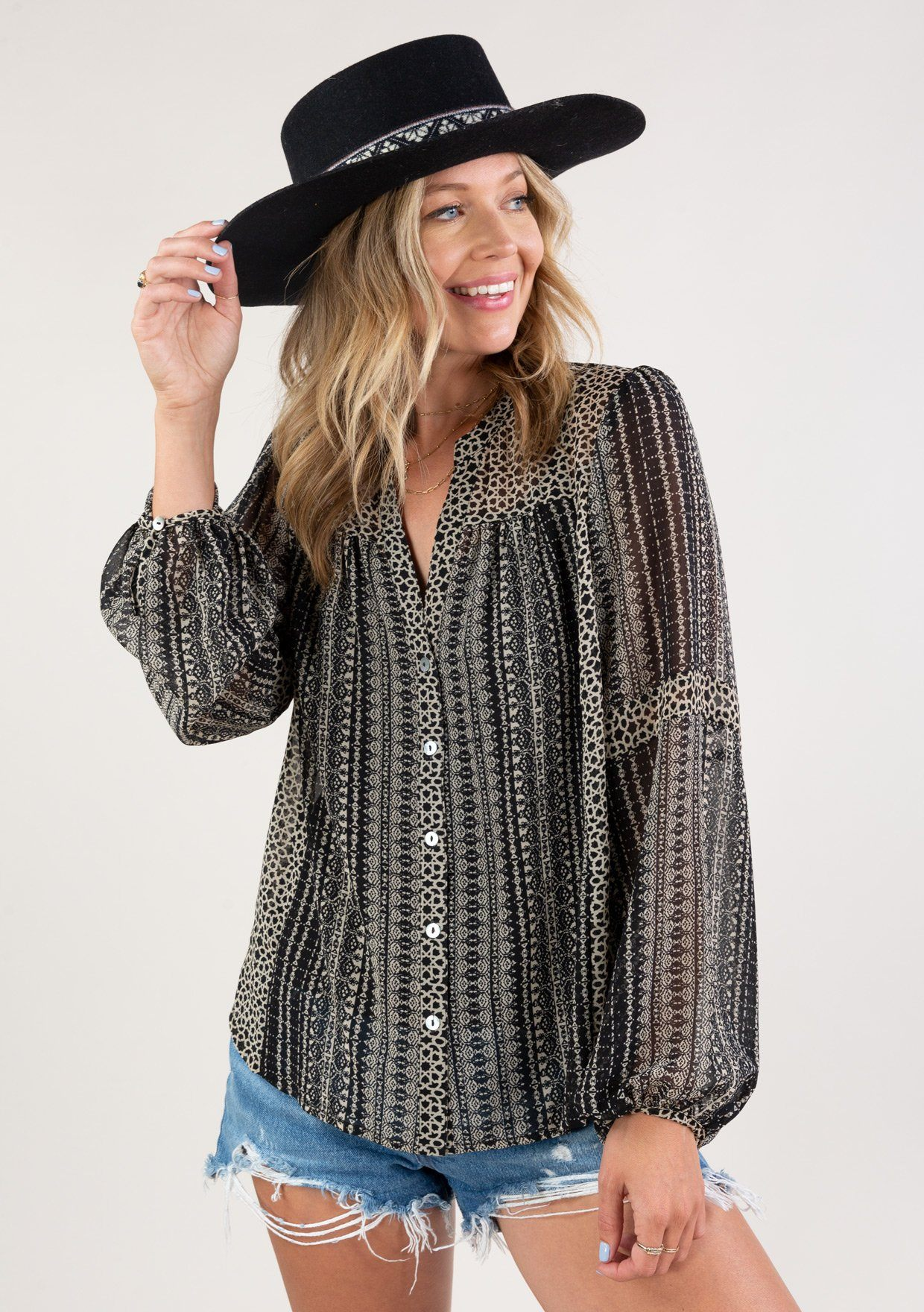 [Color: Black Cream] A versatile bohemian blouse in a mixed geometric print that will transition from Summer to Fall with ease. Featuring flattering voluminous sleeves with a single button wrist cuff closure, an easy button up front, and contrast trim details throughout. Pair it with jeans for a casual vibe, or dress it up with a skirt for a bohemian chic look.