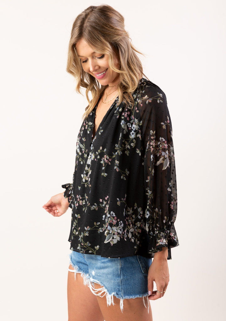 [Color: Black Slate] You will look totally adorable in our gorgeous bohemian blouse in a sheer floral clip dot chiffon. A perfect all season style that features flattering long voluminous sleeves with a flirty ruffle wrist cuff, a button up front with elegant self covered buttons, and button loop details along the v neckline.
