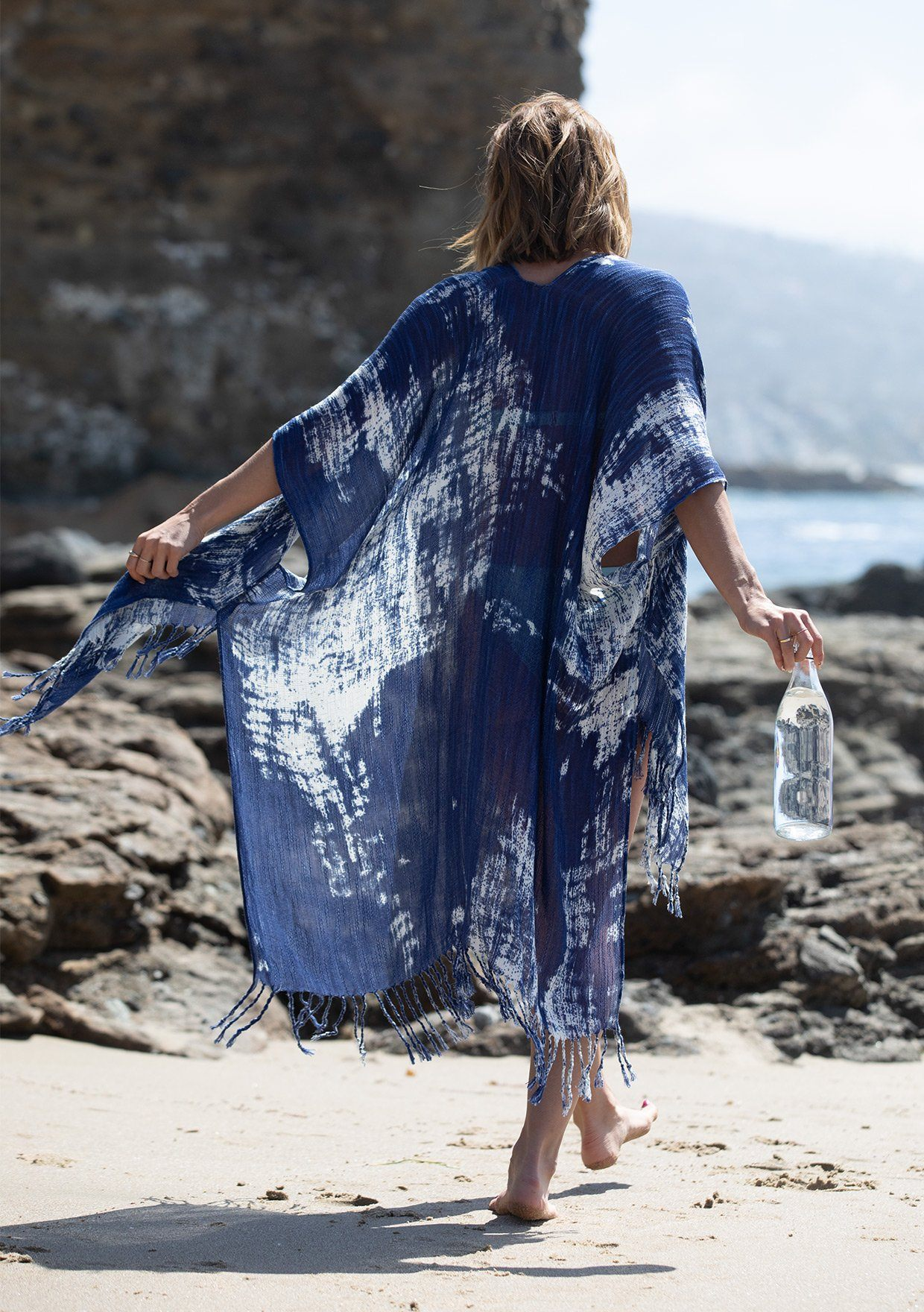 [Color: Navy] A woman standing on the beach wearing a lightweight bohemian mid length tie dye kimono. Featuring a fringed hemline, an open front, and half length kimono sleeves.