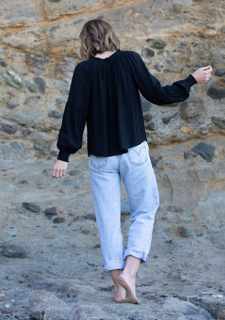 [Color: Black] A woman standing on the beach wearing a classic linen blend peasant top. Featuring a ruffled tassel tie split neckline and long voluminous sleeves with a smocked elastic wrist cuff.