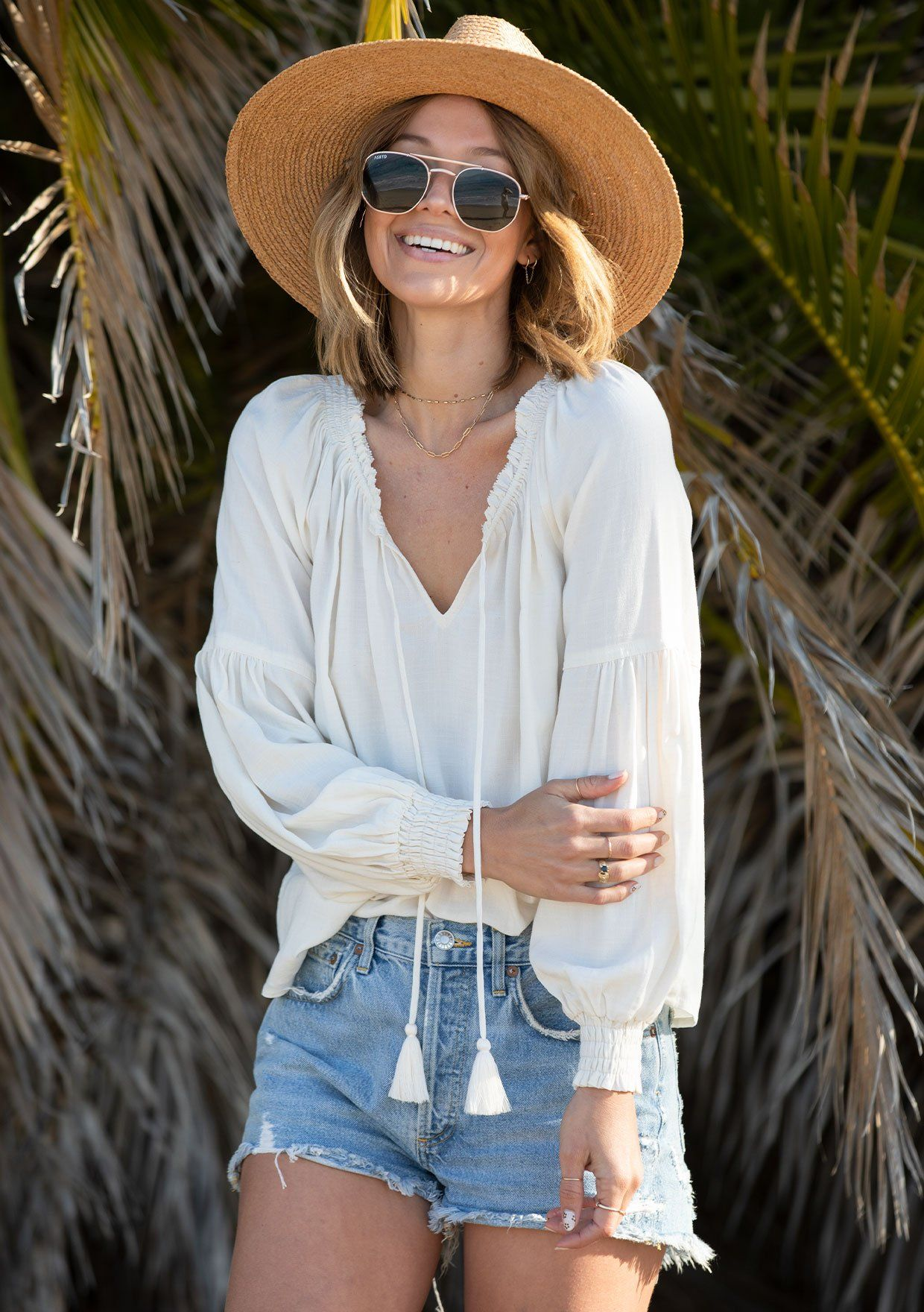 [Color: Vanilla] A woman standing on the beach wearing a classic linen blend peasant top. Featuring a ruffled tassel tie split neckline and long voluminous sleeves with a smocked elastic wrist cuff.