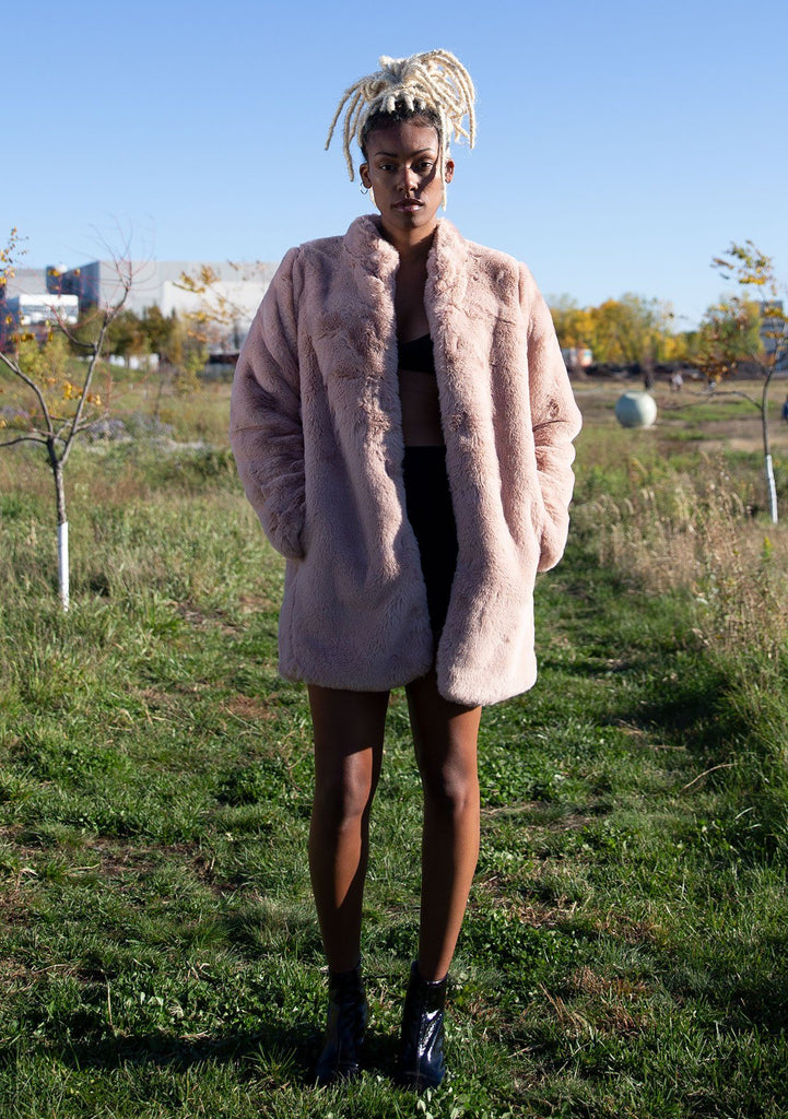 [Color: Blush] Ultra luxe faux fur statement coat in a soft pretty pink. Featuring essential side pockets, a silky lining, and a soft hand feel. Styled here with a sparkly mini dress and heels.