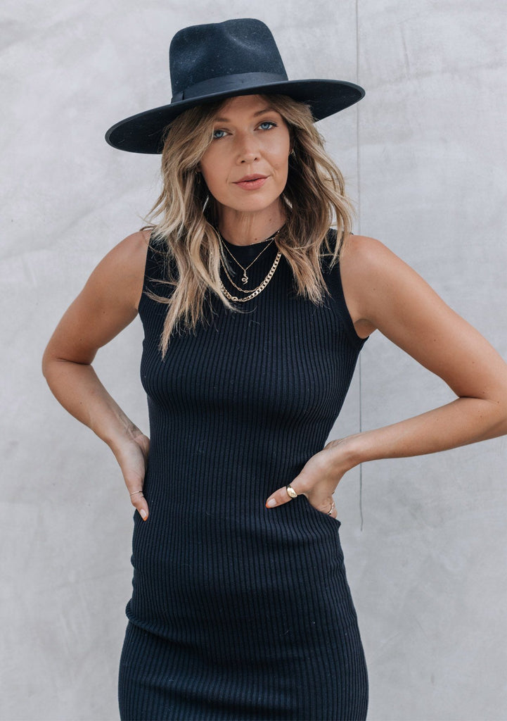 [Color: Black] Elevate your sweater dress game with our effortlessly chic sleeveless ribbed bodycon dress! A touch of stretch gives this midi dress an easy slim fit and helps to maintain its shape. Styled here with boots and a hat for a cozy Fall vibe.