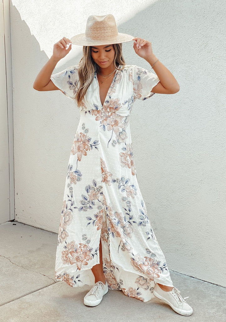 [Color: Blush Natural] A feminine floral print bohemian maxi dress in swiss dot. Featuring a button front v neckline, a high low hemline, and smocking details along the shoulders and waist. Styled here with a hat and white sneakers.