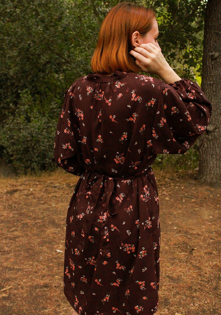 [Color: Merlot Rose] A romantic, vintage inspired floral mini dress. Featuring a v neckline, a waist defining tie back detail, and voluminous long sleeves.