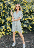 [Color: Mint/Peach] A woman standing outside in front a flowers wearing a floral print mini wrap dress. A fit and flare style that features a ruffle flounce hem and sleeve.